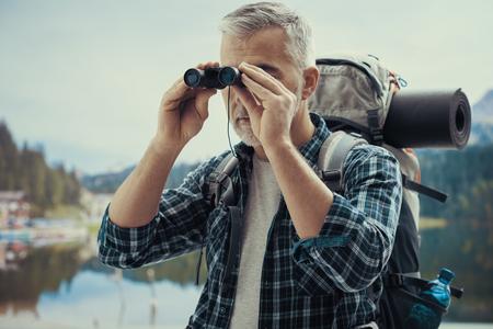 Mature hiker exploring mountains and looking through binoculars, trekking and nature concept