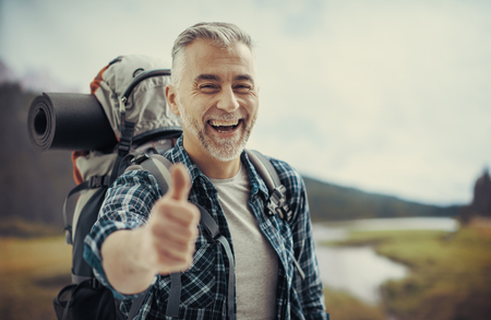 Happy mature hiker trekking on the mountains and giving a thumbs up, he is smiling at camera Stock Photo