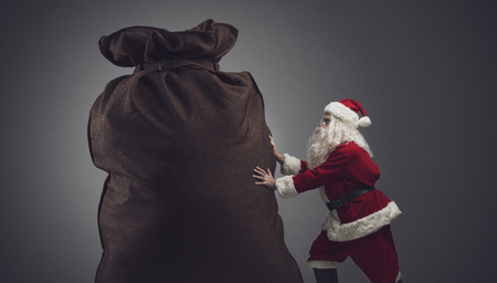Funny Santa Claus delivering a heavy big sack with Christmas gifts for kids