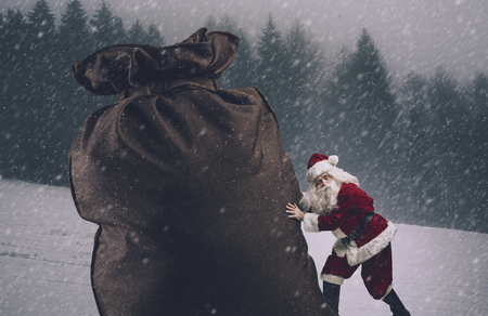 Funny Santa Claus carrying a huge sack with Christmas gifts under the snow Banco de Imagens