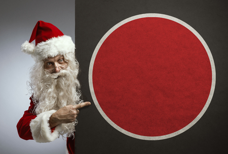 Happy traditional Santa pointing at a blank sign with copy space, Christmas advertisement concept