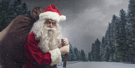 Santa carrying a big sack with Christmas gifts under the snow and wintry landscape Imagens - 114191175