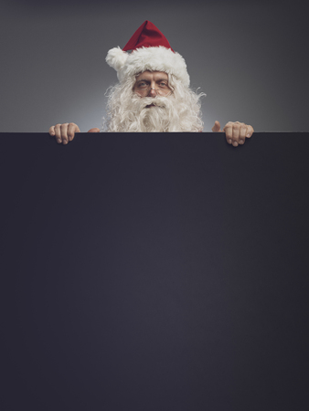 Funny Santa Claus peeking from behind Christmas advertisement blank sign with copy space, he is looking at camera