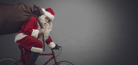 Santa Claus carrying a heavy sack with gifts for Christmas and riding a bicycle, banner with blank copy space