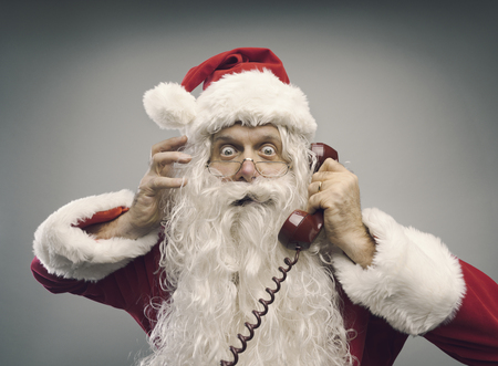 Stressed panicked Santa Claus answering phone calls on Christmas eve, he is staring at camera with eyes wide open Reklamní fotografie