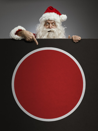 Cheerful happy Santa Claus peeking from behind a blank sign and pointing, Christmas advertisement concept