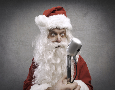 Panicked nervous Santa Claus holding a microphone before giving a speech, Christmas character Stock Photo