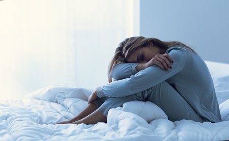 Depressed woman awake in the night, she is exhausted and suffering from insomnia