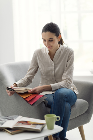 Young woman choosing the best upholstery for the armchair Stock Photo