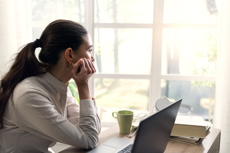 Pensive young woman using a laptop at home and looking at the window