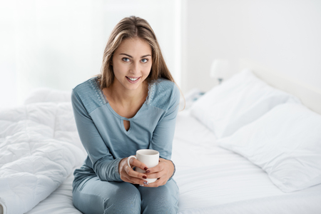 Young woman having breakfast in bed, she is drinking a coffee and smiling
