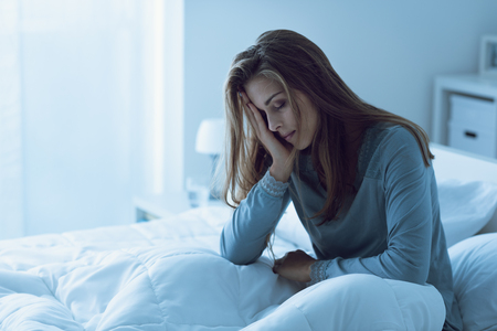 Depressed woman awake in the night, she is touching her forehead and suffering from insomnia Stock Photo