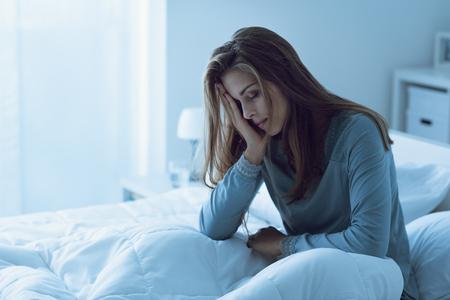 Mujer deprimida despierta en la noche, se toca la frente y sufre de insomnio