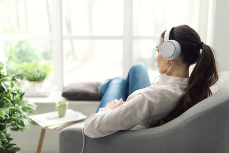 Young woman relaxing in the living room, she is resting on the couch and listening to music using headphones