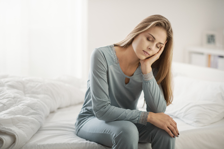 Exhausted young woman sitting on her bed in the morning an leaning on her arm, depression and sleep disorders concept