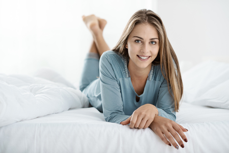 Young smiling blonde woman posing on the bed, she is lying down and smiling at camera 스톡 콘텐츠