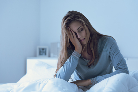 Depressed woman awake in the night, she is touching her forehead and suffering from insomnia Stockfoto