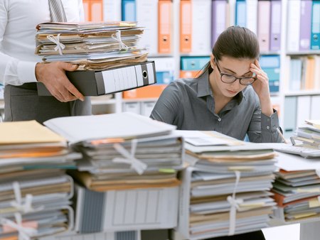 Young stressed secretary in the office overwhelmed by work and desk full of files, her boss is bringing more paperwork to her Stock Photo