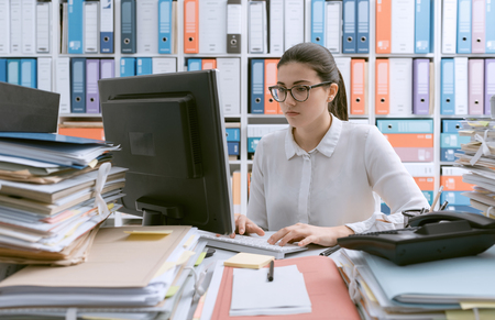 Young confident businesswoman working at office desk and piles of paperwork Stok Fotoğraf