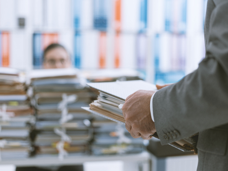 Demanding boss bringing more work to his young overloaded employee