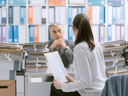 Business meeting in the office: a woman is showing paperwork to a business executive