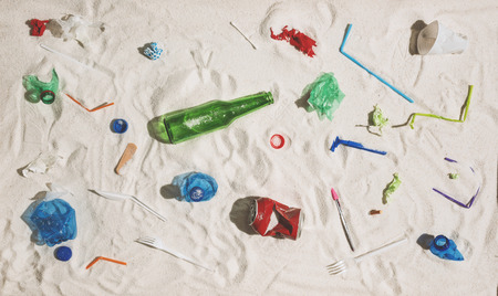 Polluted beach with plastic, glass waste and assorted rubbish: environmental protection and plastic pollution concept Stock Photo