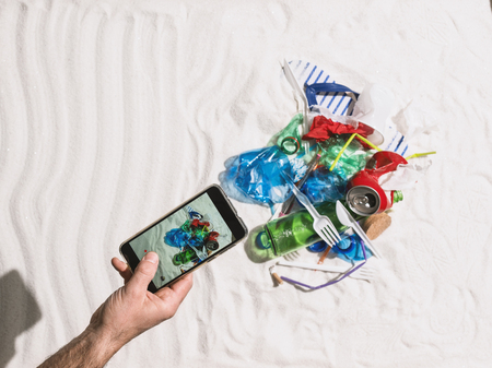 Man taking a picture of waste pollution on the beach and sharing it online using his smartphone, environmental protection and plastic pollution concept