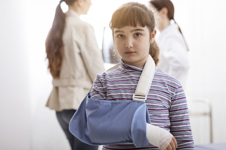 Girl with broken arm in the doctors office, she is wearing an arm brace and looking at camera