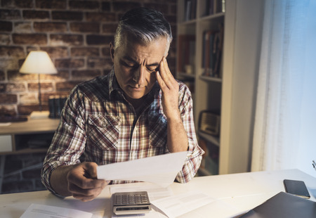 Worried mature man checking his domestic bills at home, he is concerned and reading his financial statements Foto de archivo