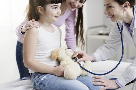 Doctor visitando a una linda niña y jugando con ella, ella está revisando los latidos del corazón del oso de peluche con un estetoscopio, niños y concepto de salud