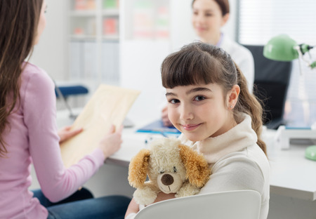 Cute girl in the doctors office, she is hugging her teddy bear, children and healthcare concept 版權商用圖片