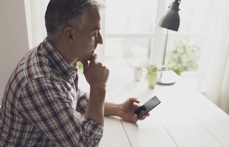 Uomo in possesso di uno smartphone e in attesa di una telefonata, comunicazione e concetto di tecnologia Archivio Fotografico