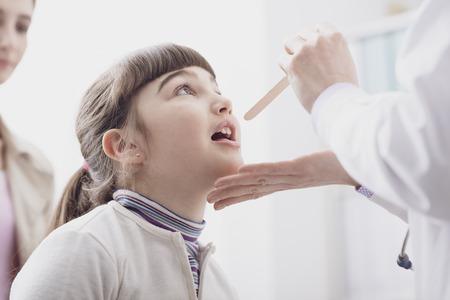 Professionele arts die de keel van een meisje controleert, ze opent haar mond