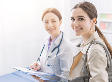 Young female doctor meeting a patient in the office and smiling, medicine and healthcare concept 写真素材
