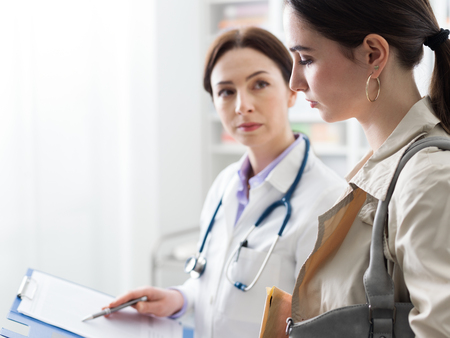 Doctor meeting a patient in the office and showing medical records, they are serious and concerned