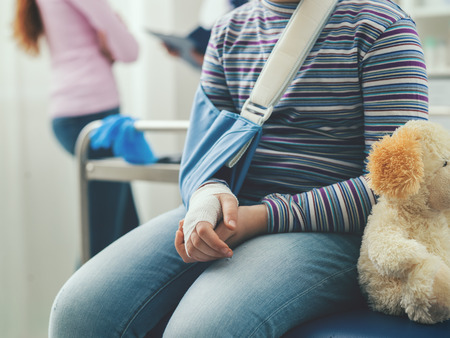 Cute girl in the doctor's office waiting to be visited, she is sitting on the examination couch with her teddy bear