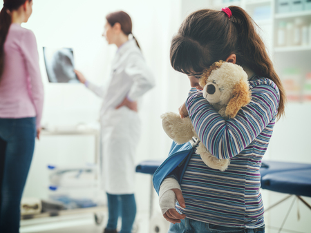 Scared cute girl with arm brace in the doctors office, she is holding a teddy bear plushie, children and healthcare concept Stockfoto
