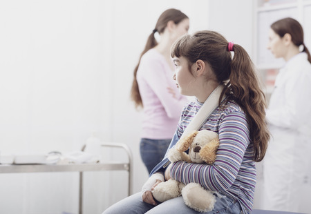 Cute girl with broken arm waiting to be visited in the doctors office, she is holding her teddy bear