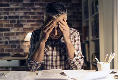 Desperate mature man checking his domestic bills at home, he is holding an invoice and touching his head