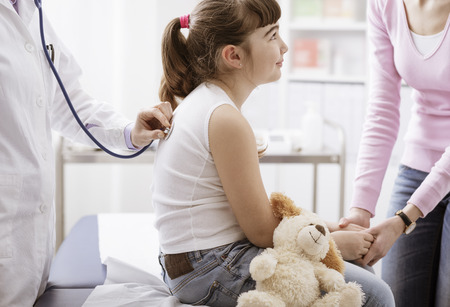Female doctor examining a cute smiling girl with a stethoscope, the mother is next to her, children and healthcare concept Stock Photo