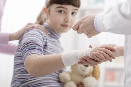 Dottoressa che avvolge il polso ferito di una ragazza con una benda e una garza, la ragazza tiene in mano il suo orsacchiotto Archivio Fotografico
