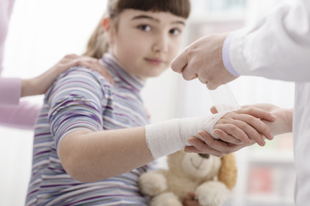 Female doctor wrapping a girl's injured wrist with a bandage and gauze, the girl is holding her teddy bear