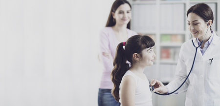 Female doctor examining a cute smiling girl with a stethoscope, the mother is next to her, children and healthcare concept 写真素材