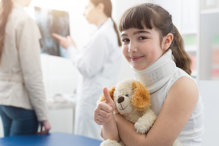 Cute girl with cervical collar in the doctors office: she is smiling, holding her teddy bear and giving a thumbs up