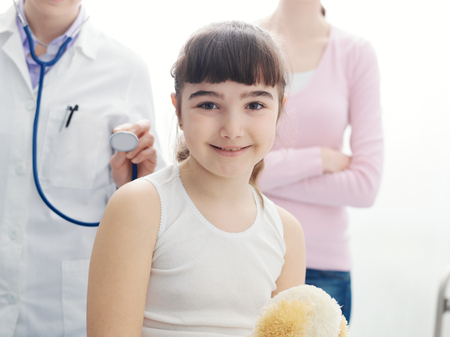 Happy smiling girl in the doctors office during a visit, healthcare and childhood concept