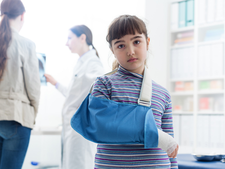 Cute sad girl with broken arm in the doctors office, she is wearing an arm brace and looking at camera Фото со стока