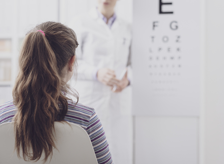 Oculist testing a young patients eyesight using an eye chart, ophthalmology and eyesight concept Stock fotó