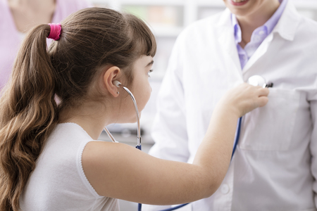 Friendly doctor playing with a young patient during a visit: the girl is examining the doctor with a stethoscope