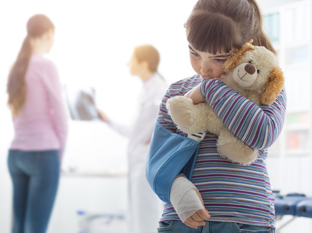 Scared cute girl with arm brace in the doctors office, she is holding a teddy bear plushie, children and healthcare concept Imagens