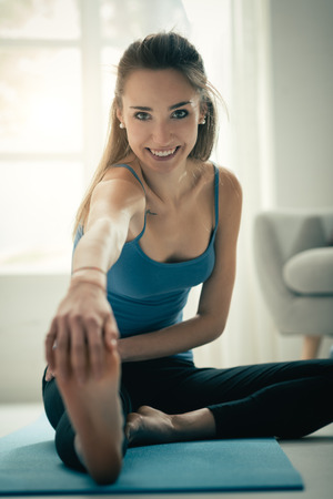 Confident young woman sitting on the floor at home and doing a stretching exercise for her legs